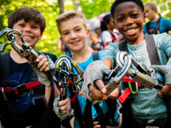 three boys holding harness for ziplining