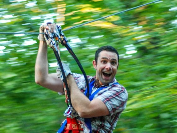 Adult man zip lining