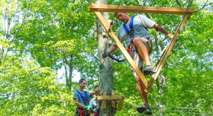 Adults going through a wooden triangle obstacle on the high ropes course