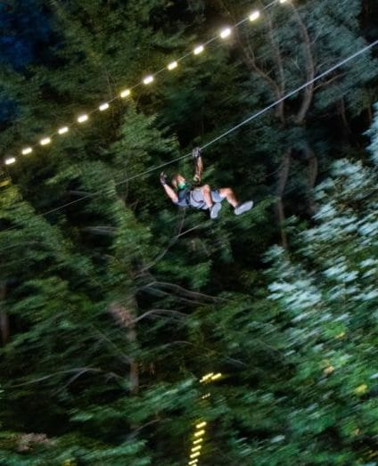 man ziplining at night